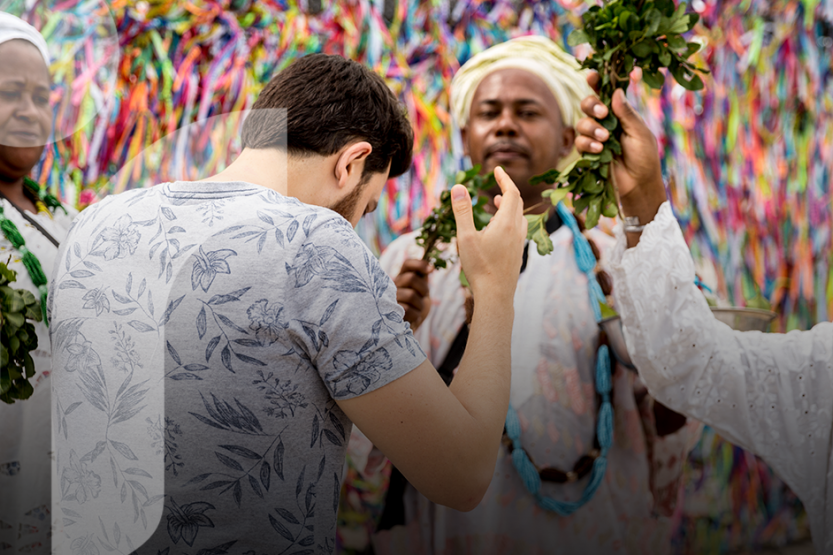 A man in a floral shirt is being blessed by three healers in white, traditional outfits