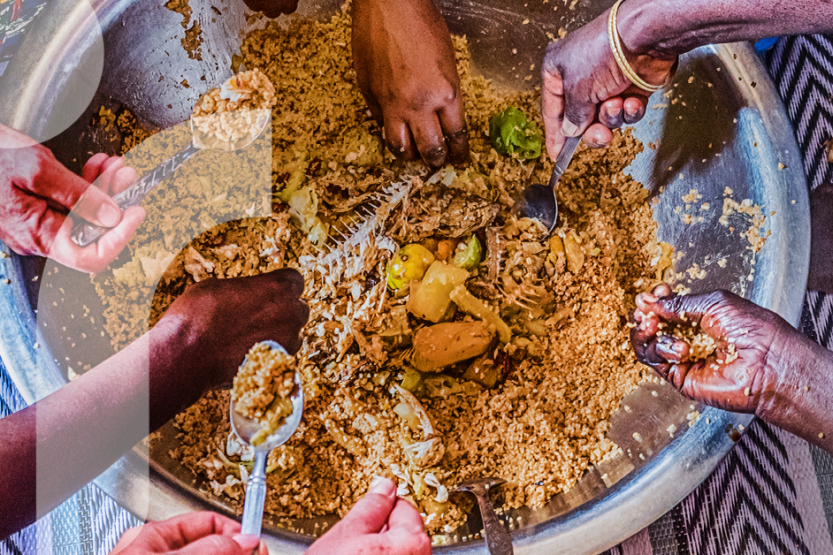 Seven hands are reaching into a communal dish of rice and fish