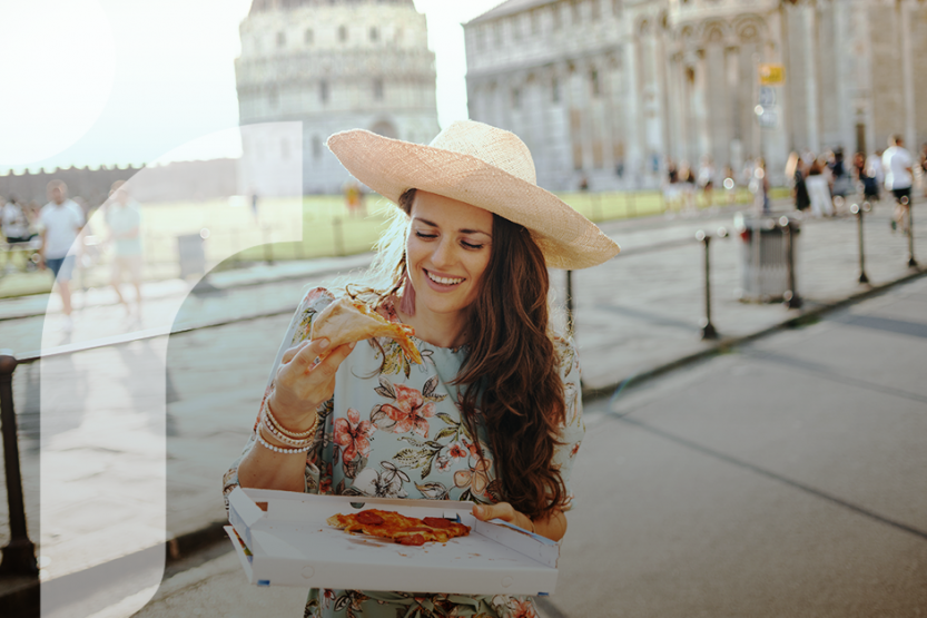 A woman in a floral dress and straw hat eats a slice of pizza in front of a Roman cityscape