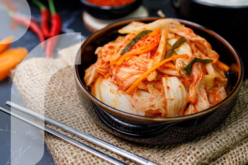 Kimchi in a black bowl is placed on top of a burlap table covering near silver metal chopsticks