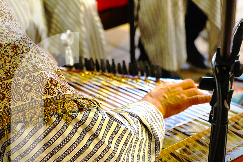A person in traditional Syrian clothing plays a string instrument
