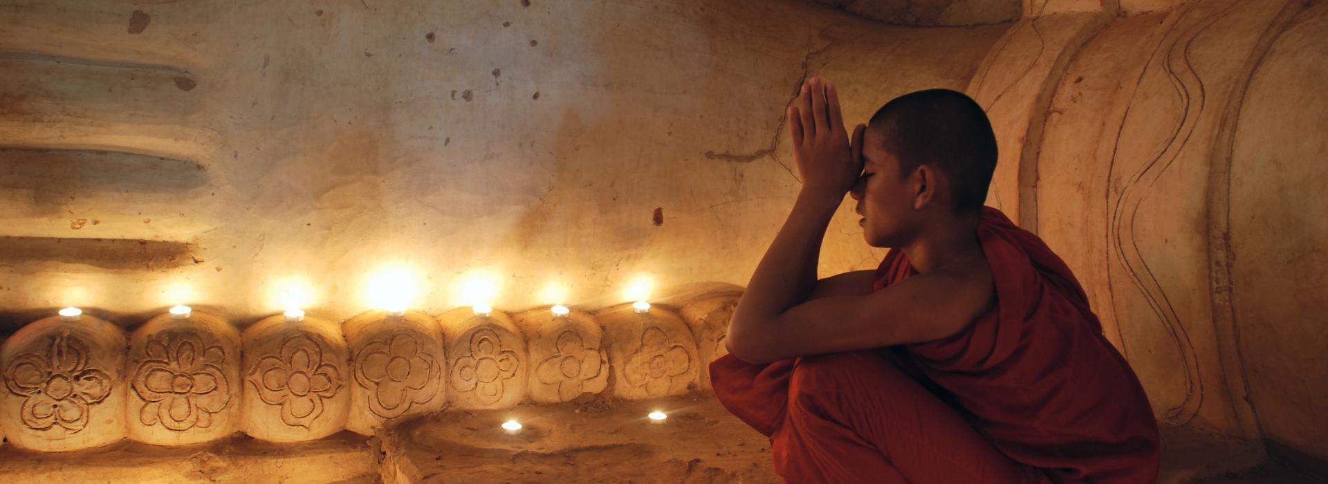 Young man in candlelit stone temple praying.
