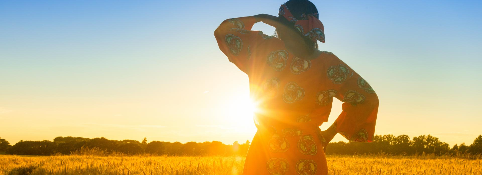 Woman standing in grasslands against sunset.