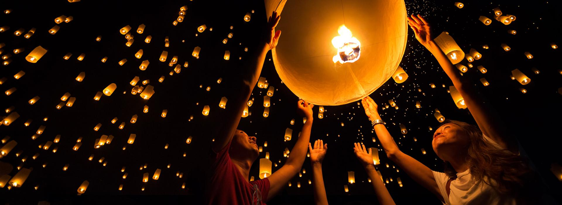 People releasing lanterns into the sky at night.