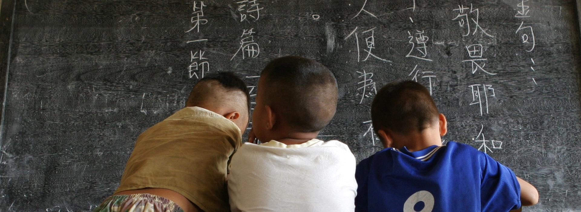 Asian children writing on a chalkboard