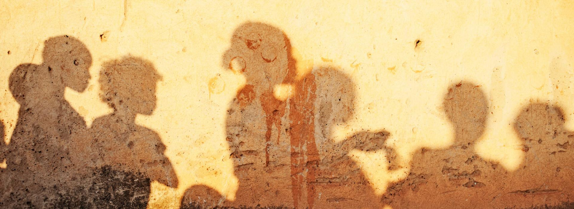 Group of children's shadows on a yellow-beige mud or plaster wall.